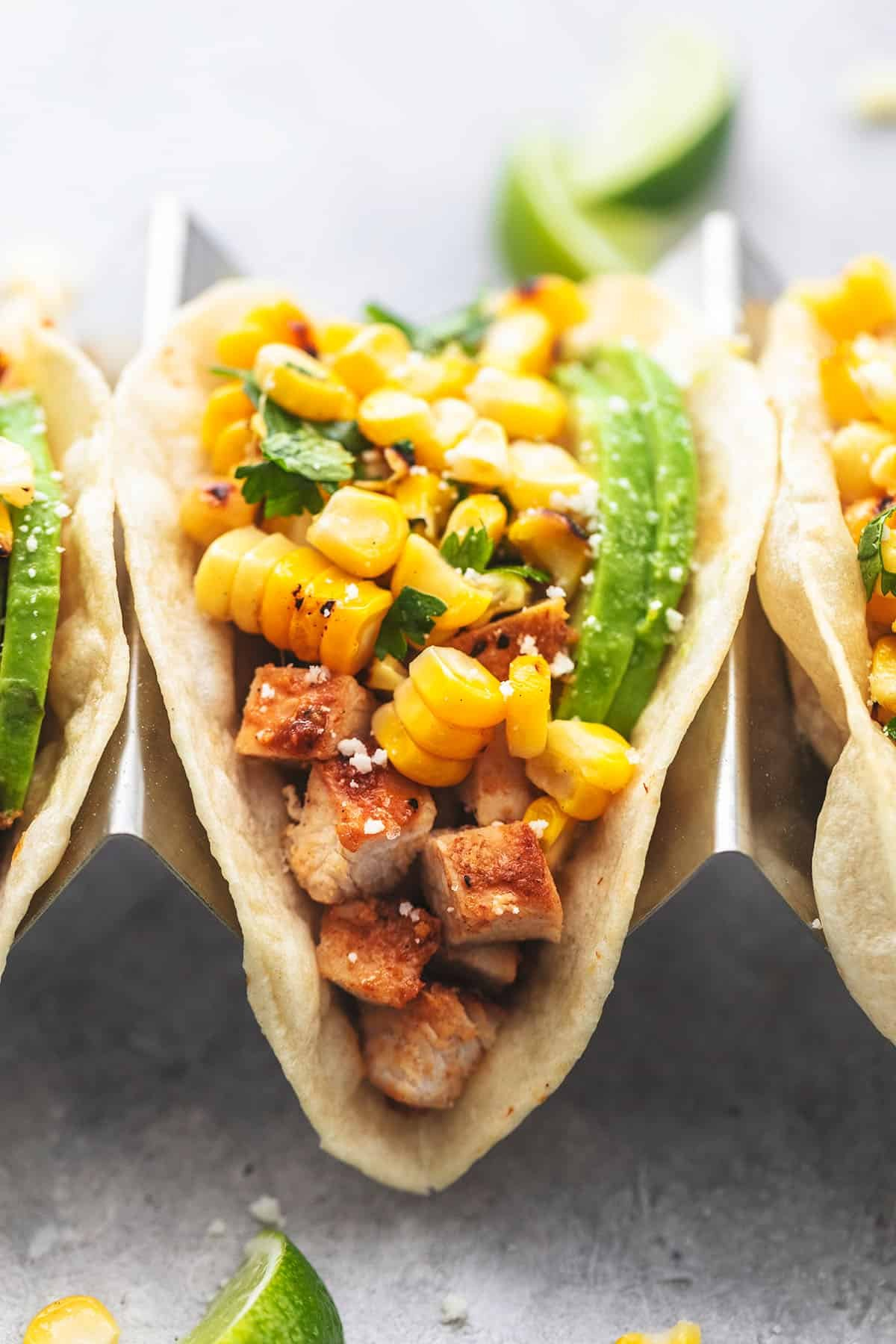 up close single taco filled with chicken in taco holder topped with corn salsa