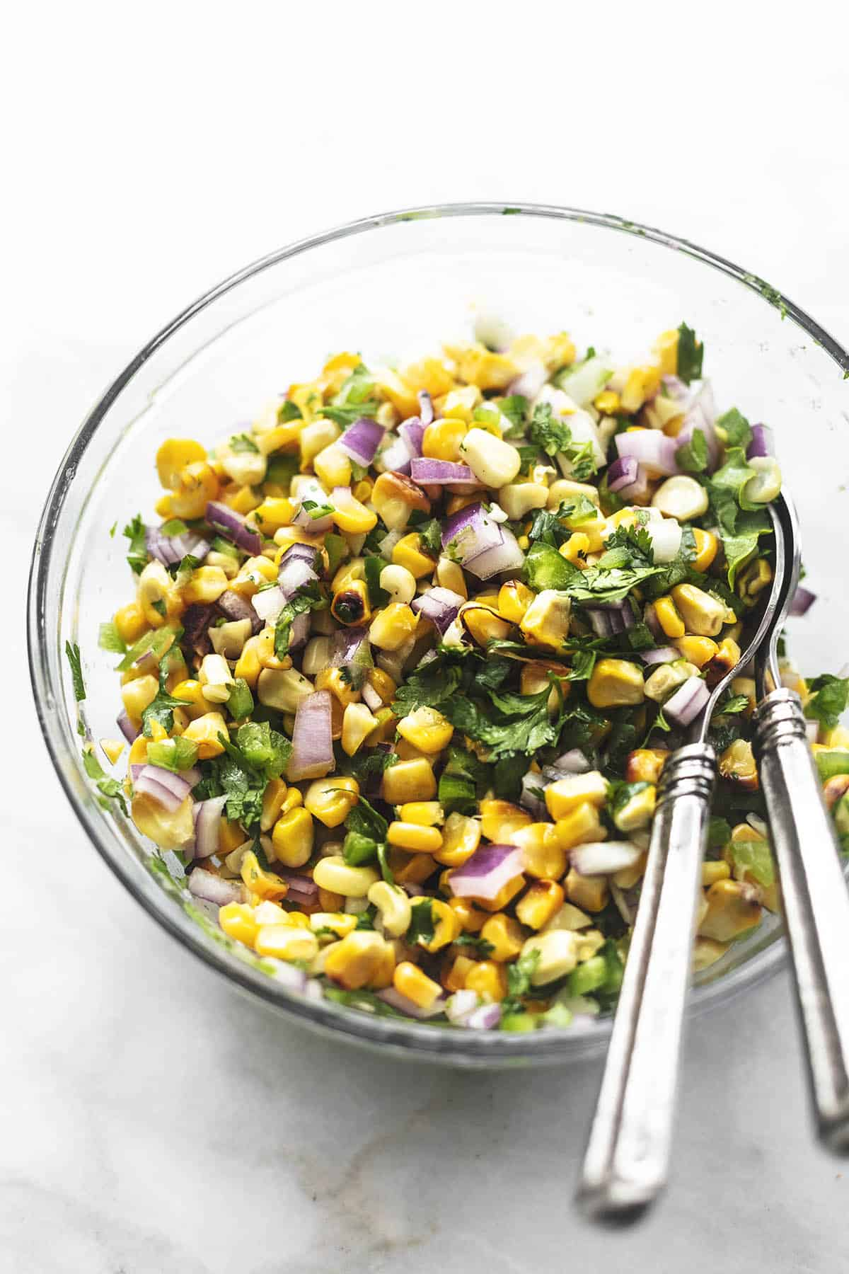 corn salsa in a glass bowl with two serving spoons on marble tabletop.