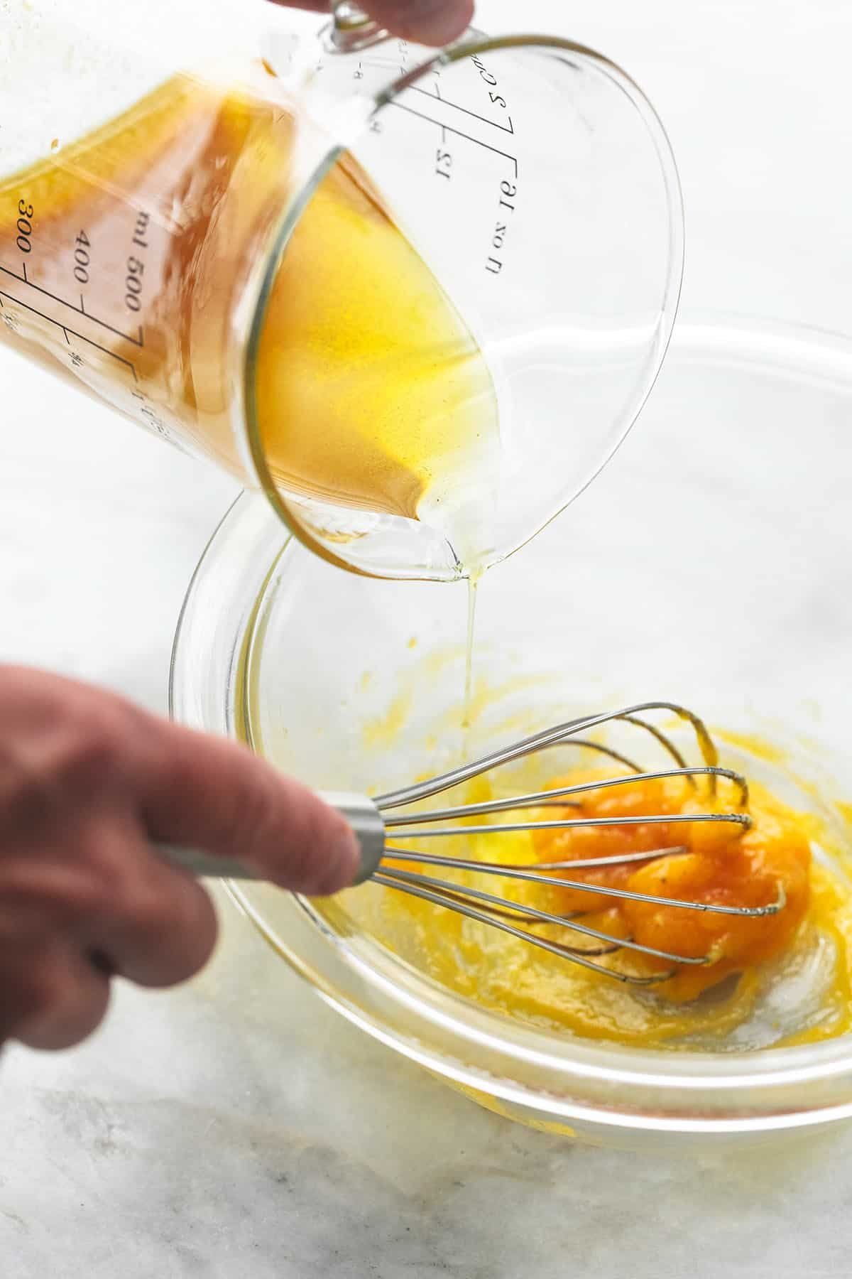 hands whisking egg yolks in glass bowl and pouring olive oil into bowl