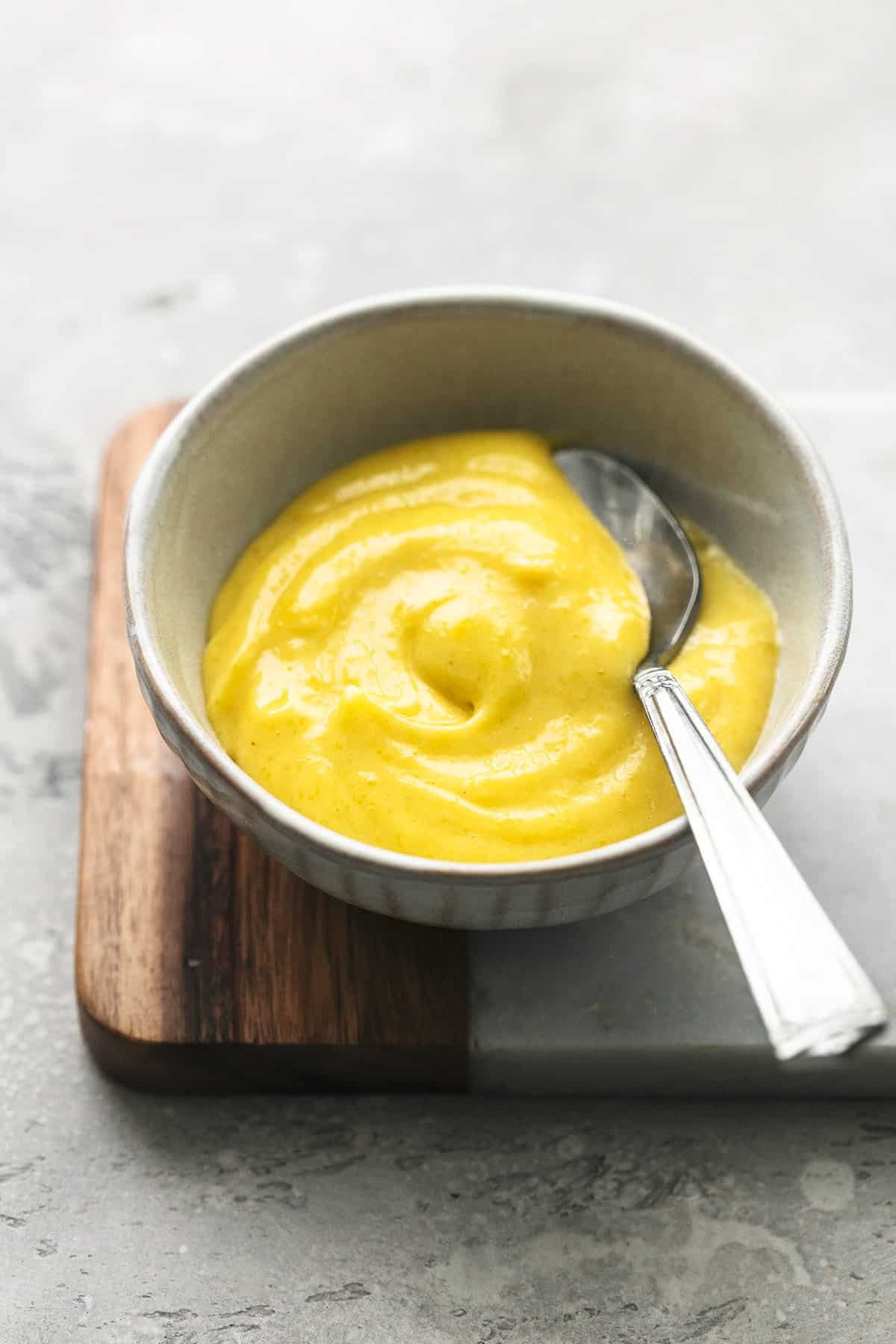 garlic aioli in small bowl with spoon on top of cutting board