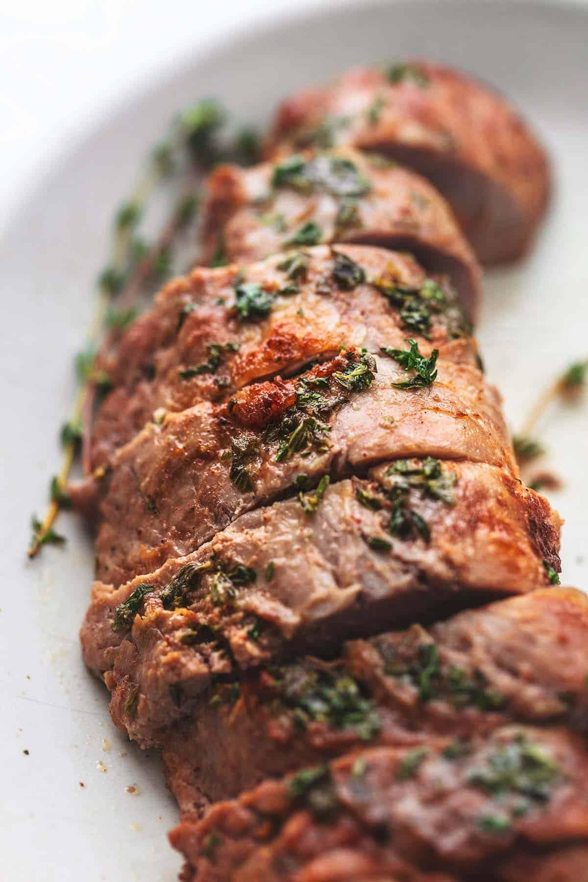 close up ofgarlic butter roasted pork tenderloin with herbs on top.