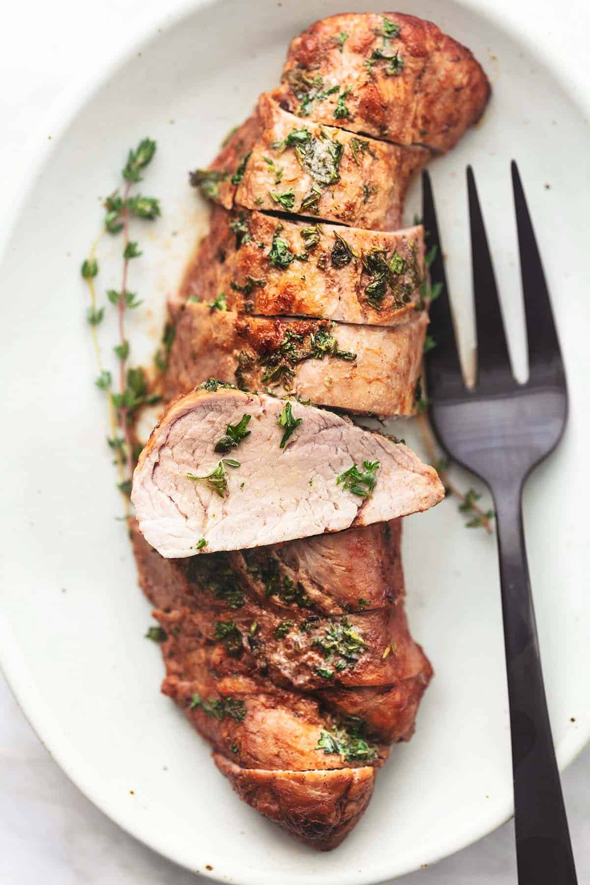 close up top view of garlic butter roasted pork tenderloin sliced on a platter with a serving fork.