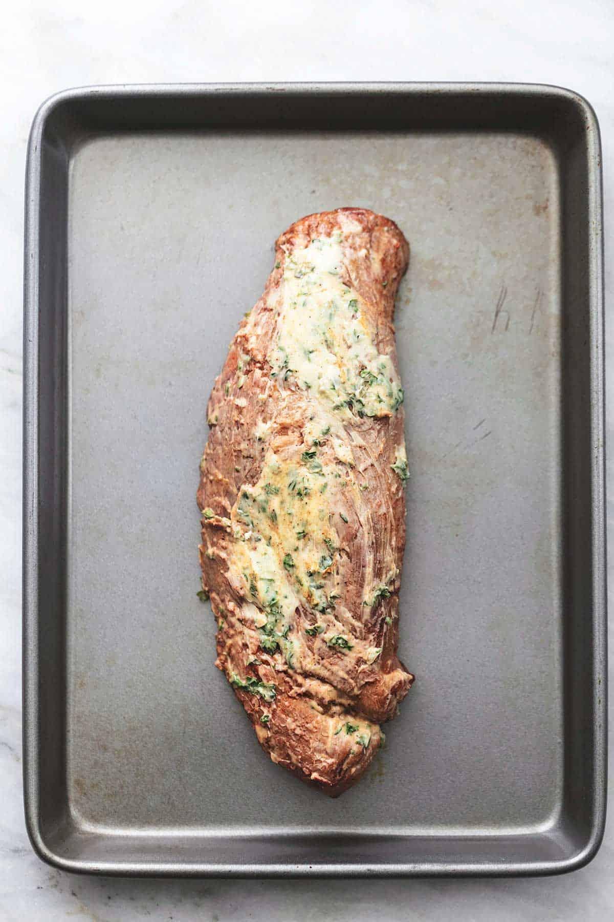 top view of garlic butter rubbed on uncooked garlic butter roasted pork tenderloin on a baking sheet.
