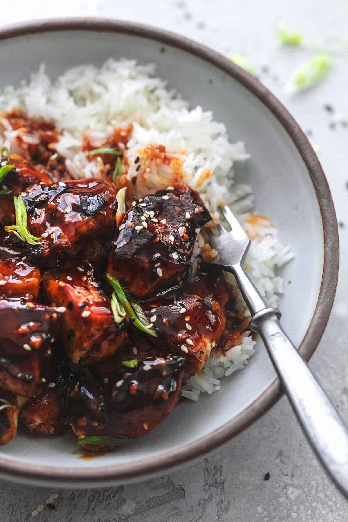 up close Korean bbq chicken with dark red sauce and fork in bowl
