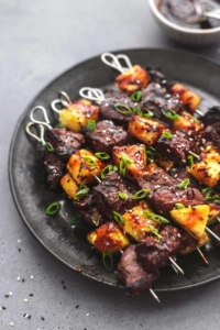 steak skewers with pineapple on a black plate