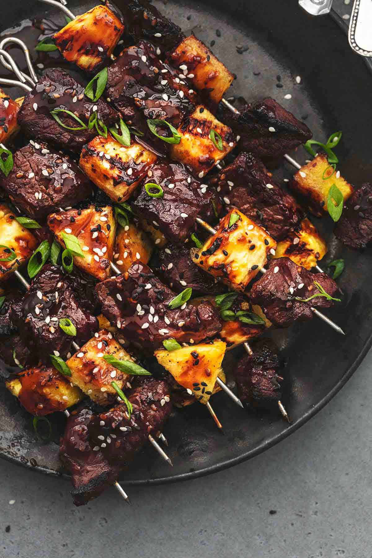 overhead beef and pineapple on metal skewers on black plate