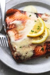 cooked salmon with butter sauce on top and lemon slices