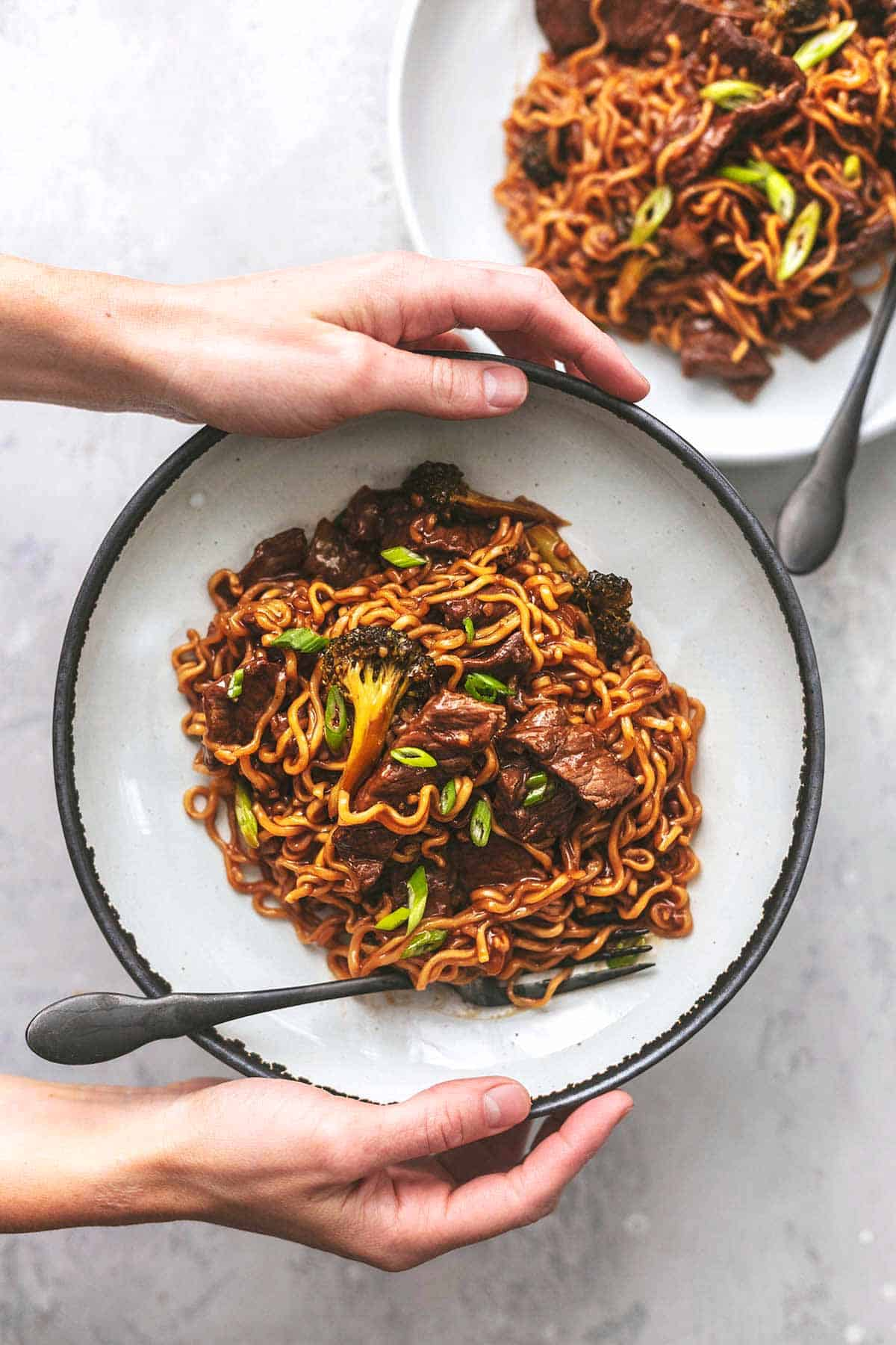 overhead view of hands holding a plate of mongolian beef and noodles