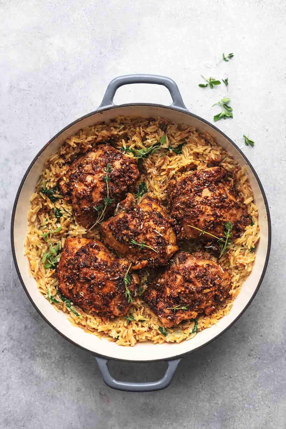 overhead view of one pot Greek chicken with herbs and creamy orzo in a pan