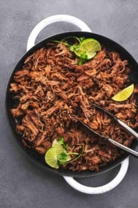 overhead view of tongs holding shredded pork with lime wedges in a cast iron pan