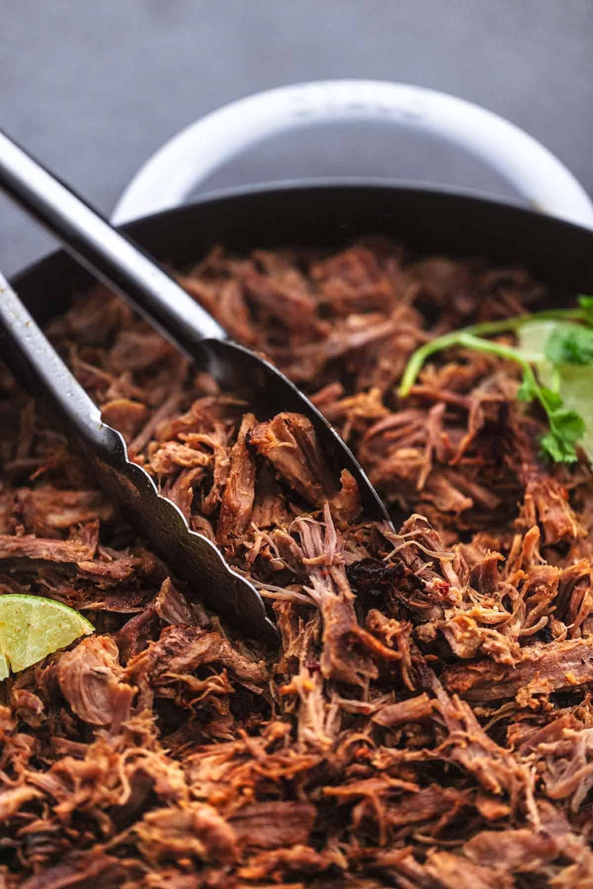 up close shredded pork held by tongs in a skillet