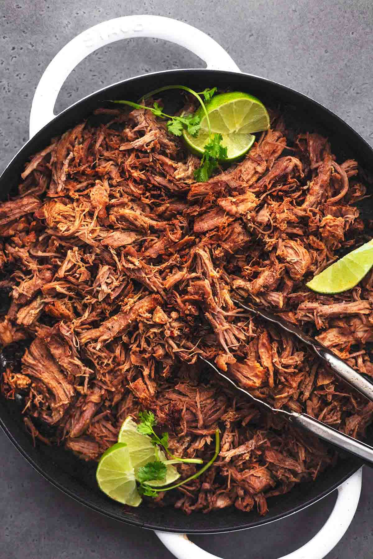 shredded meat with limes in a skillet
