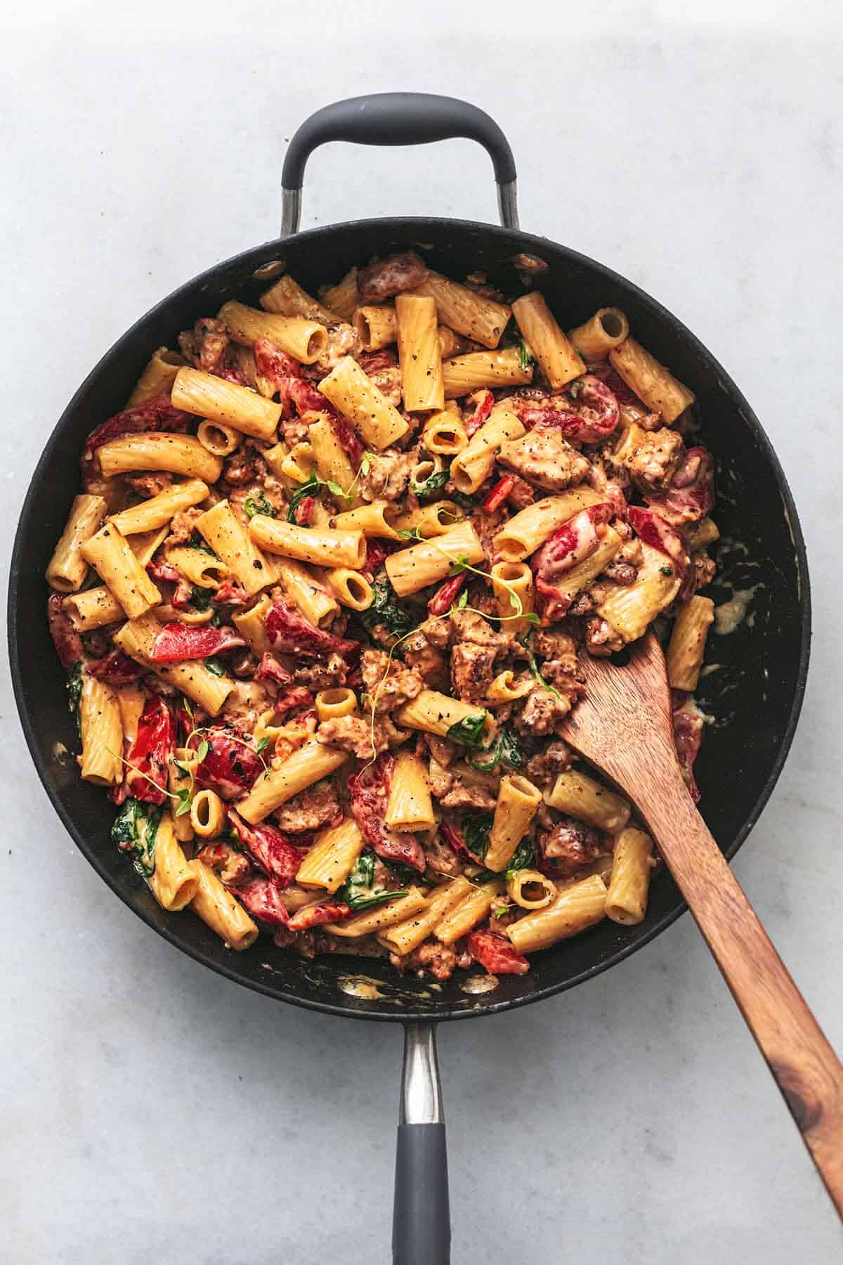 creamy pasta with roasted red peppers in a skillet with wooden spatula