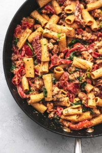 1/3 of a a black skillet filled with creamy pasta with red peppers and fresh thyme on top