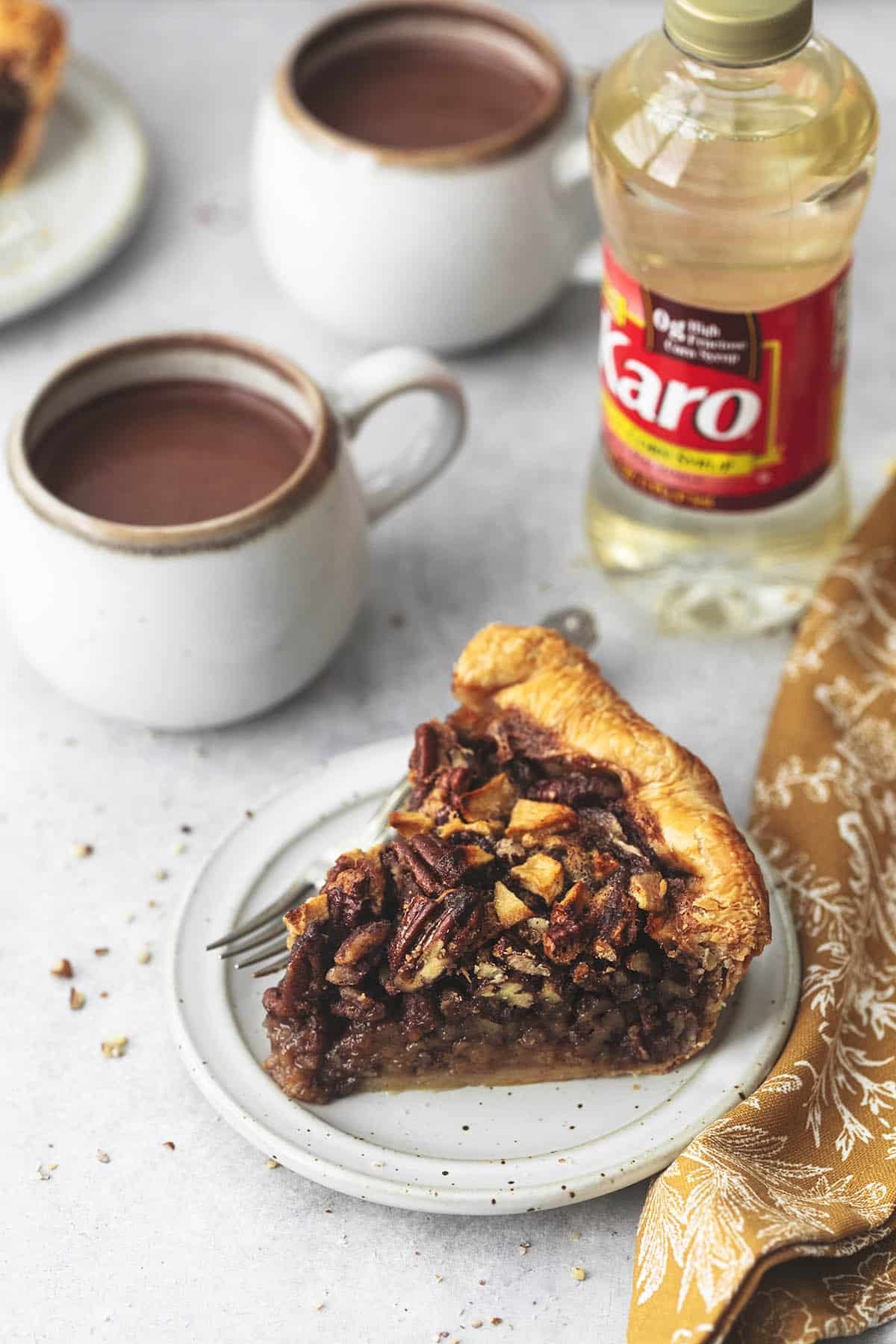 45 degree angle view of pie on plate with cup of hot chocolate and bottle of karo syrup