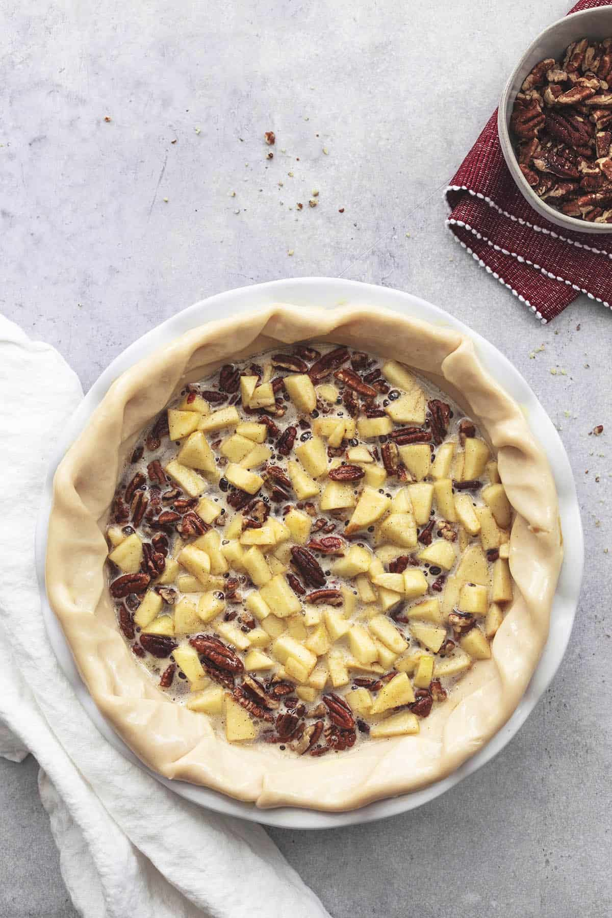 overhead view of unbaked apples and pecans in unbaked pie crust