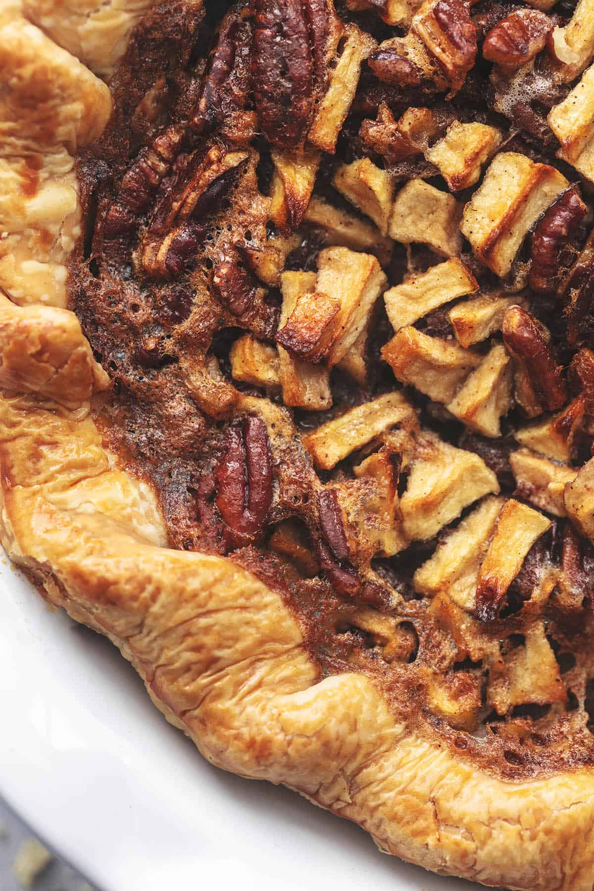 overhead up close view of apple and pecan pie with crust in white dish