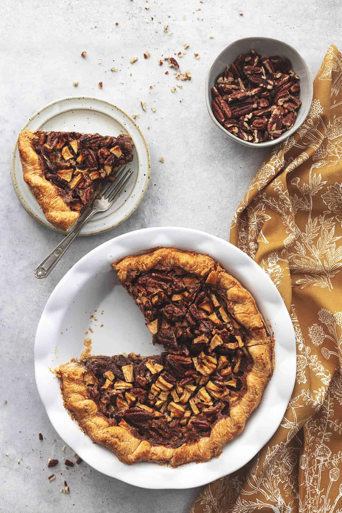 pie slice on plate beside remaining pie in dish with napkin and bowl of pecans