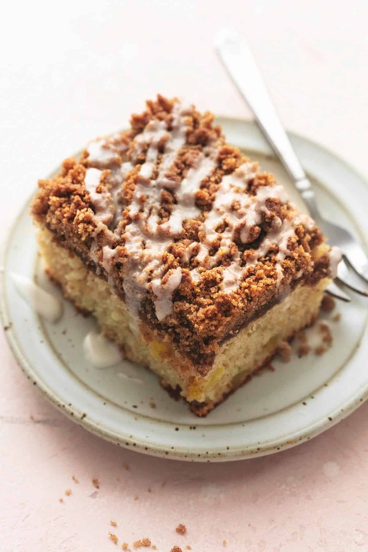 one piece of crumb cake with glaze on top on a small plate with fork