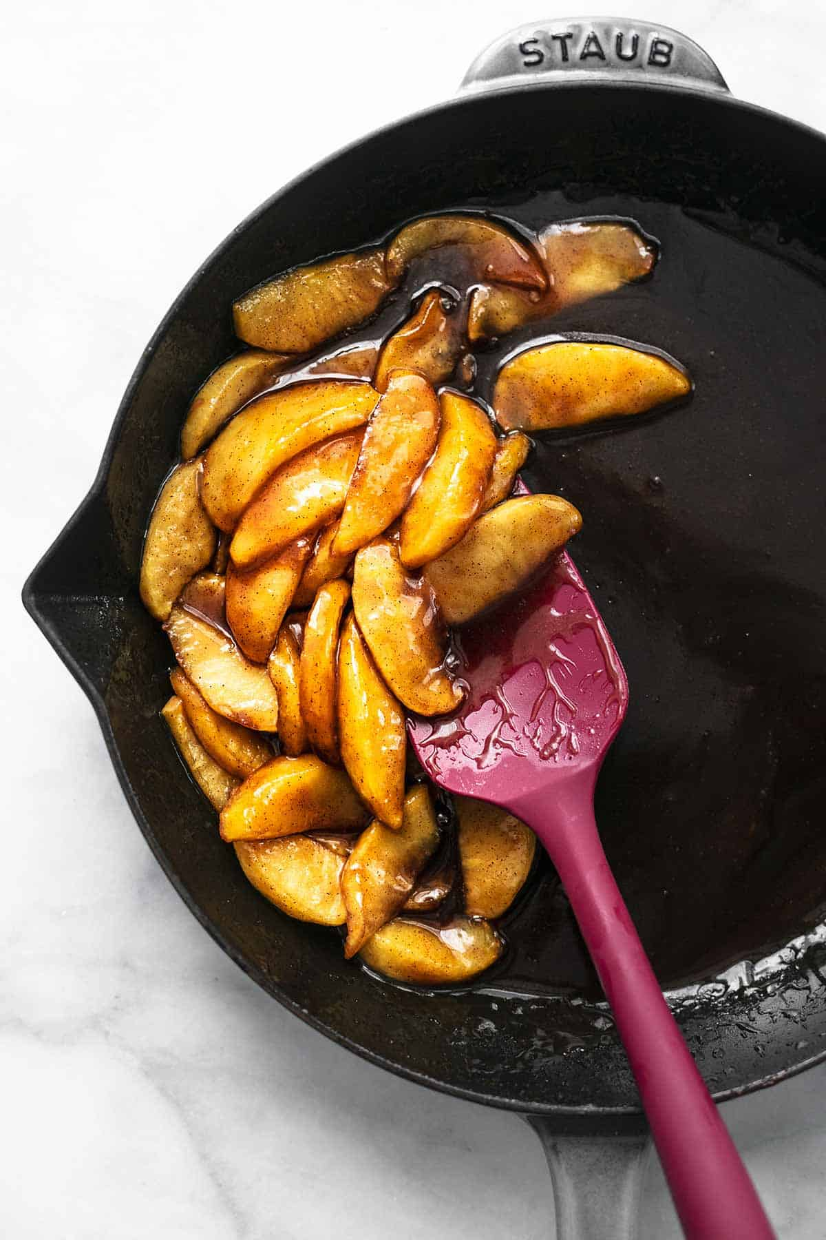 overhead view of apple compote in a skillet with a rubber spatula