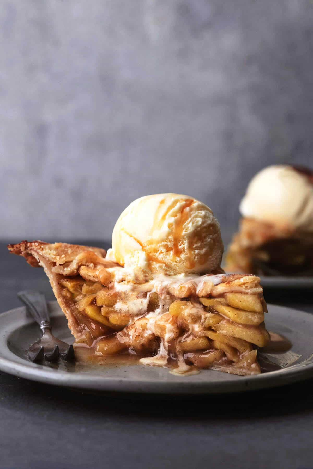 tabletop view of slice of apple pie with ice cream scoop on top