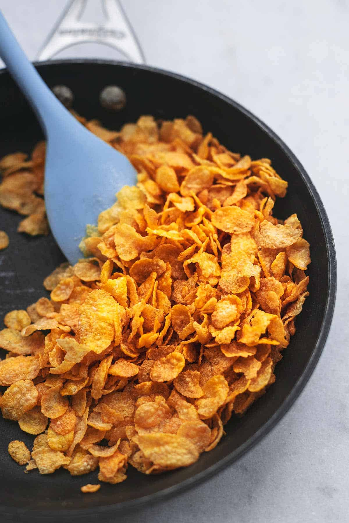 browned corn flakes in a skillet with a blue rubber spatula