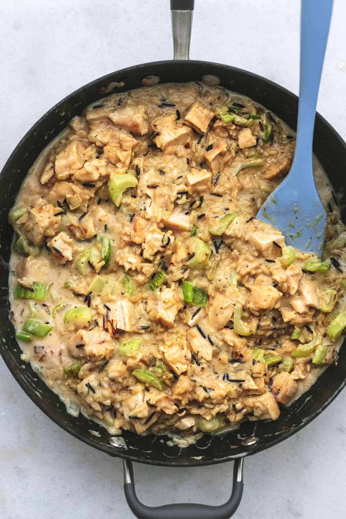 overhead view of skillet filled with chicken, rice, and celery with blue rubber spatula