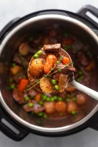 overhead view of ladle filled with beef stew above pot filled with more beef stew