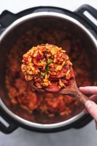 overhead view of hand holding wooden serving spoon with rice and sausage over instant pot