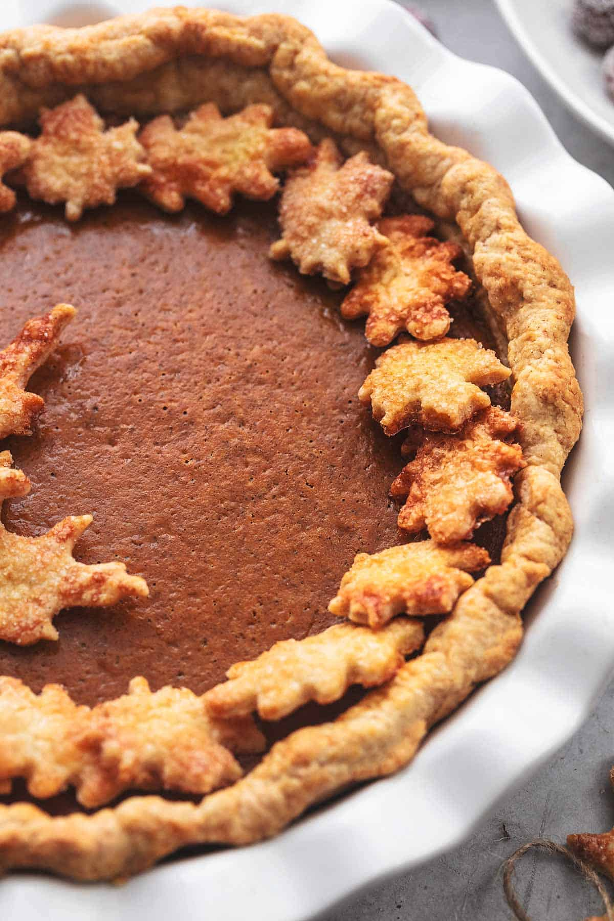 close up of pumpkin pie with golden crust and small crust leaves in a pie pan.