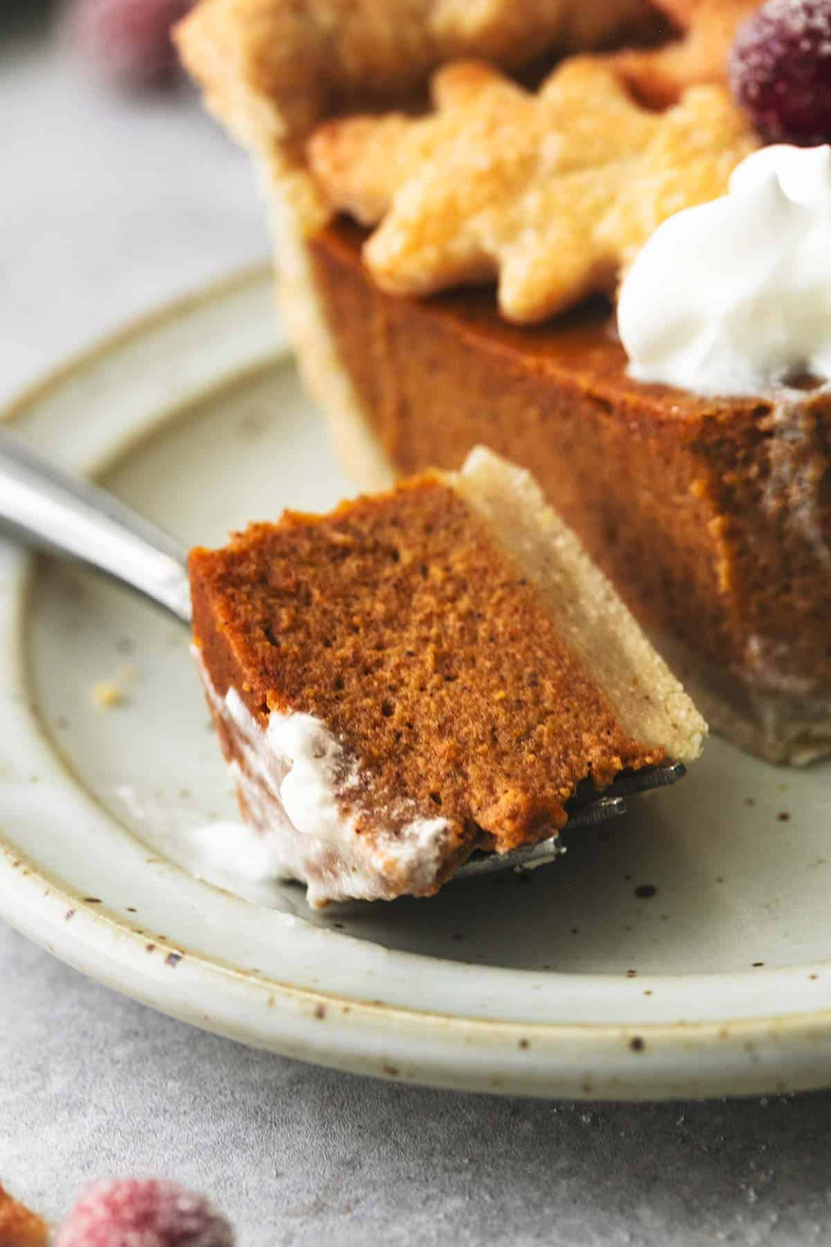 up close view of single bite of pumpkin pie with shortbread crust on a fork