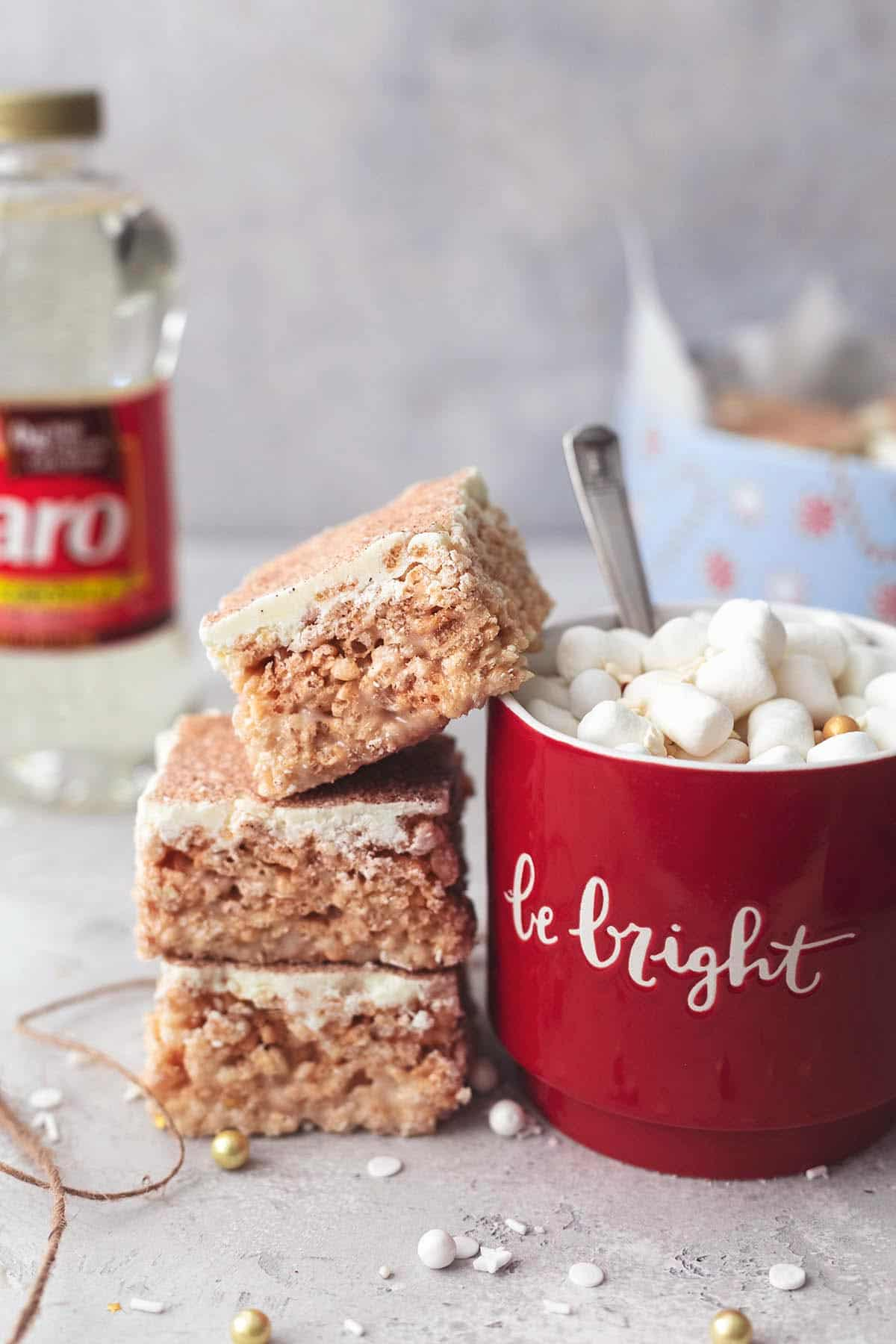 a stack of churro Krispie bars with the top bar leaning on a mug of hot chocolate with a bottle of Karo Corn Syrup and a holiday tin of more bars in the background.