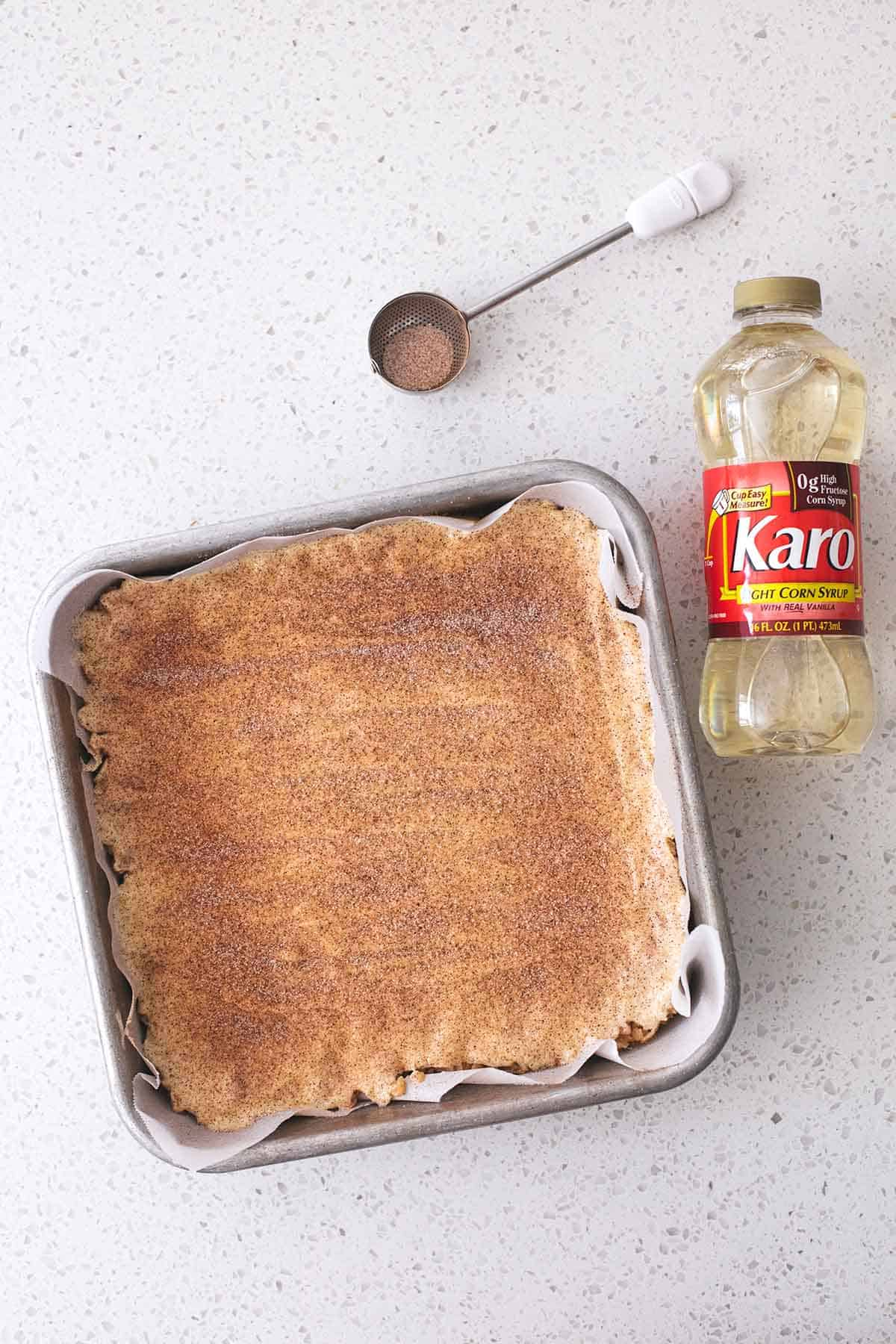 corn syrup on countertop with cinnamon-sugar topped dessert in square pan