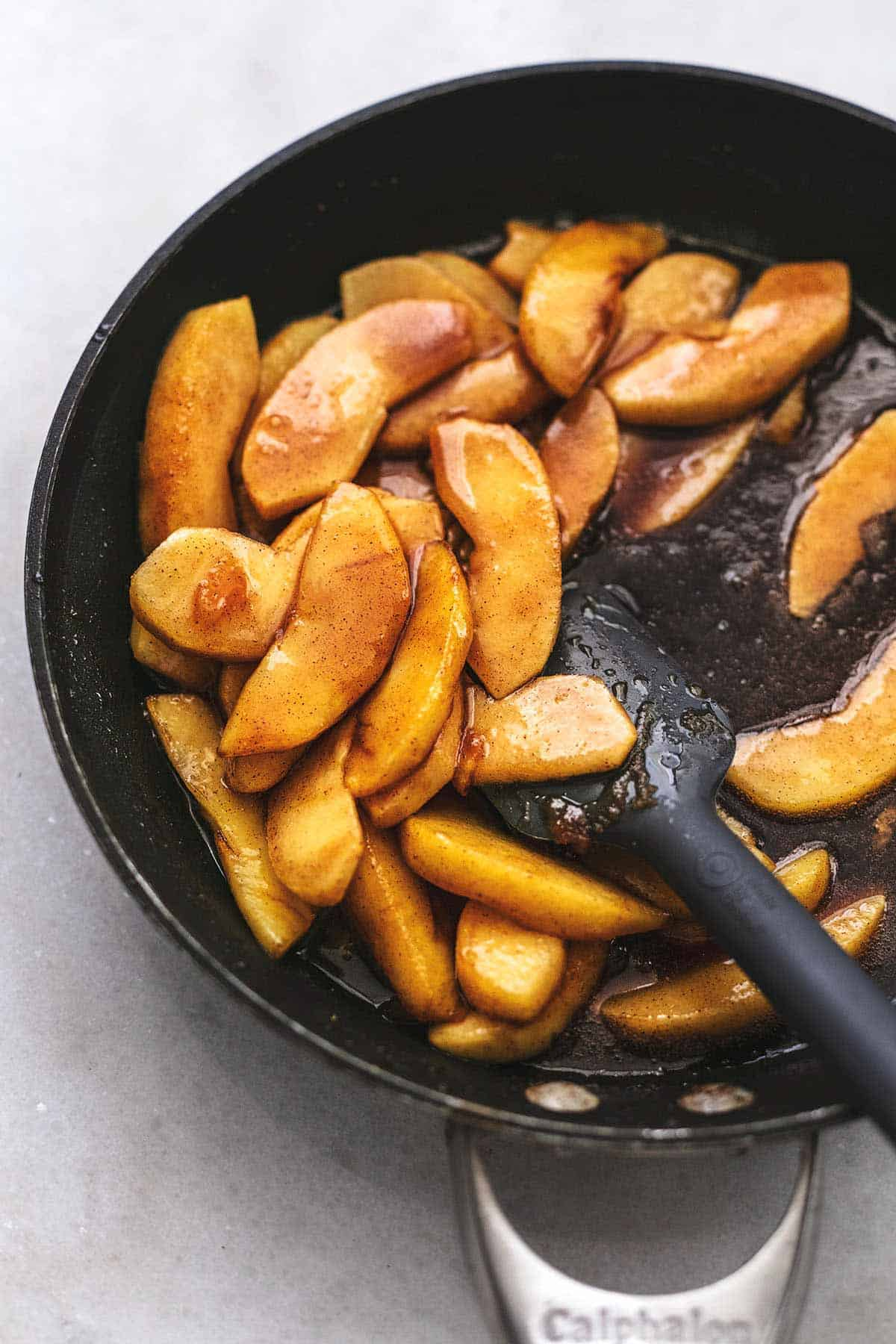 sautéed apple slices in caramel sauce in a skillet with a rubber spatula.
