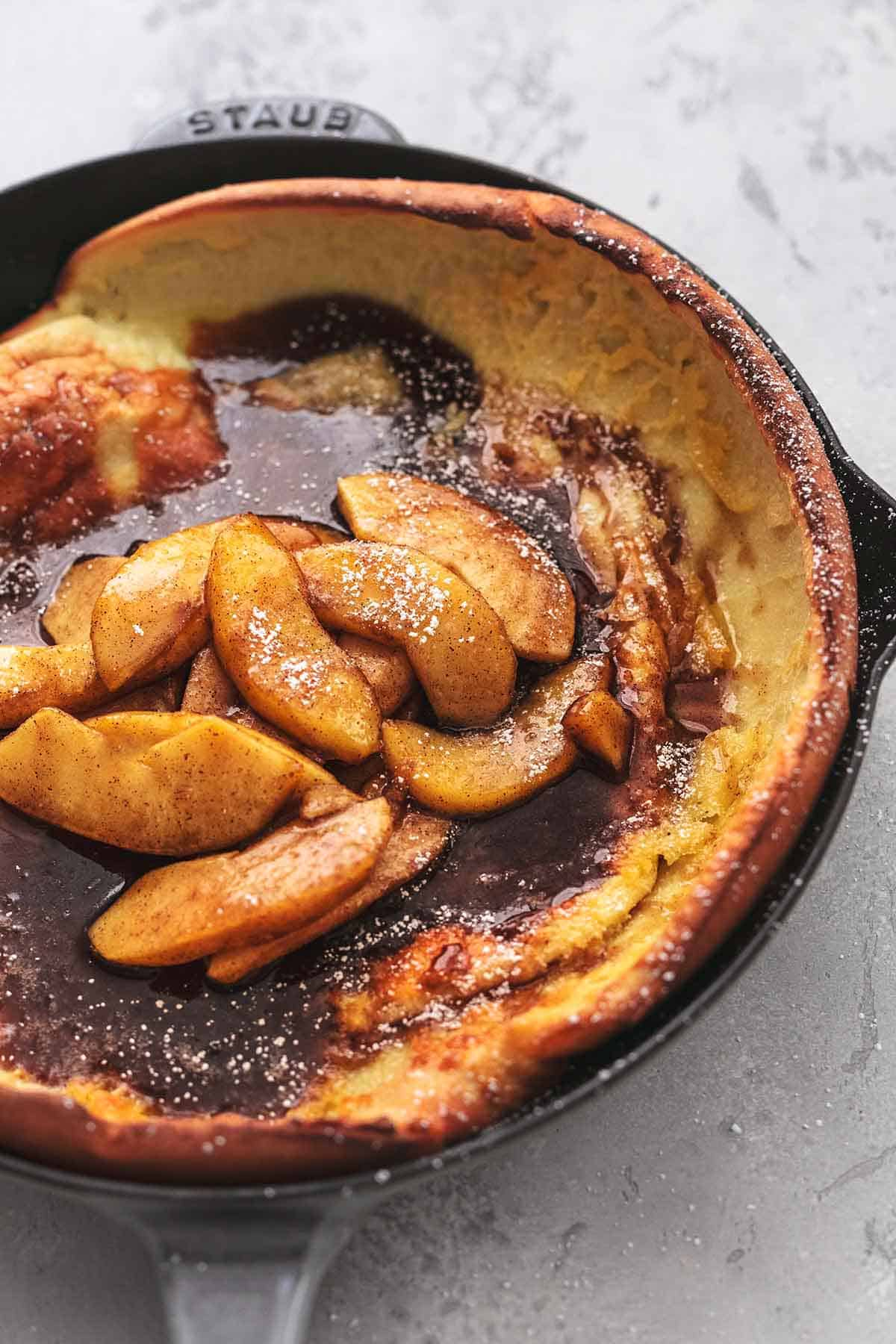 cast iron skillet with pancake and sliced apples and dark sauce
