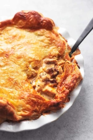 chicken and mushroom pie with black serving spoon in white pie dish