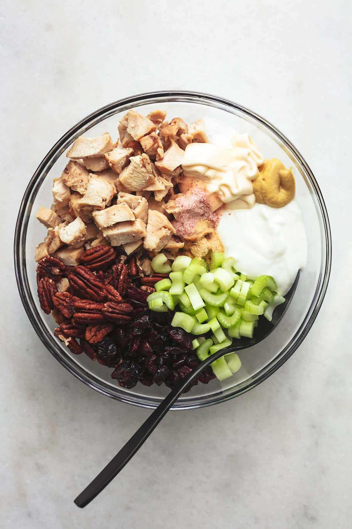 celery, turkey, greek yogurt, pecans, dried cranberries and seasonings in clear glass bowl