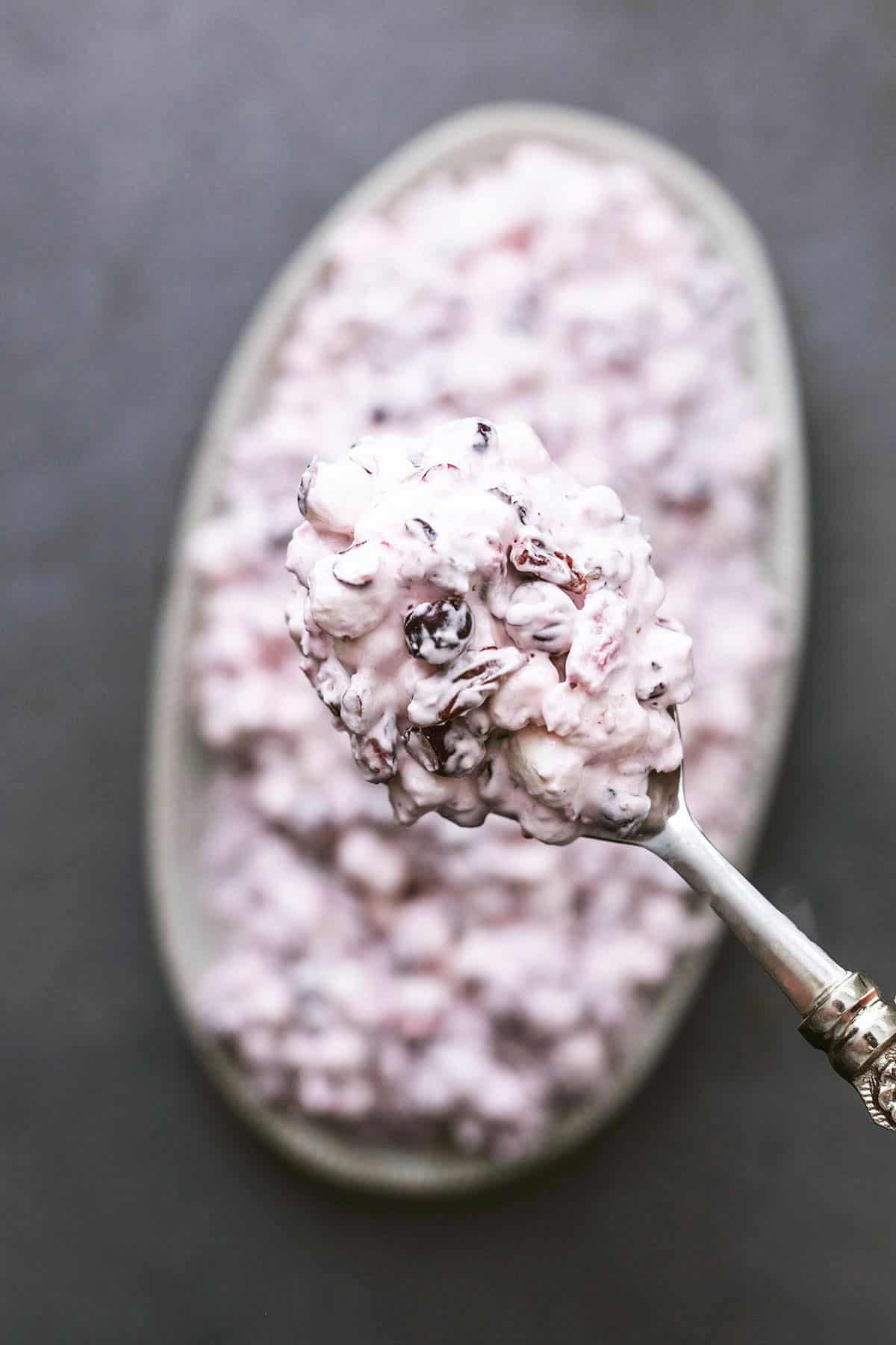 serving spoon full of marshmallow and cranberry fluff above more salad in a platter