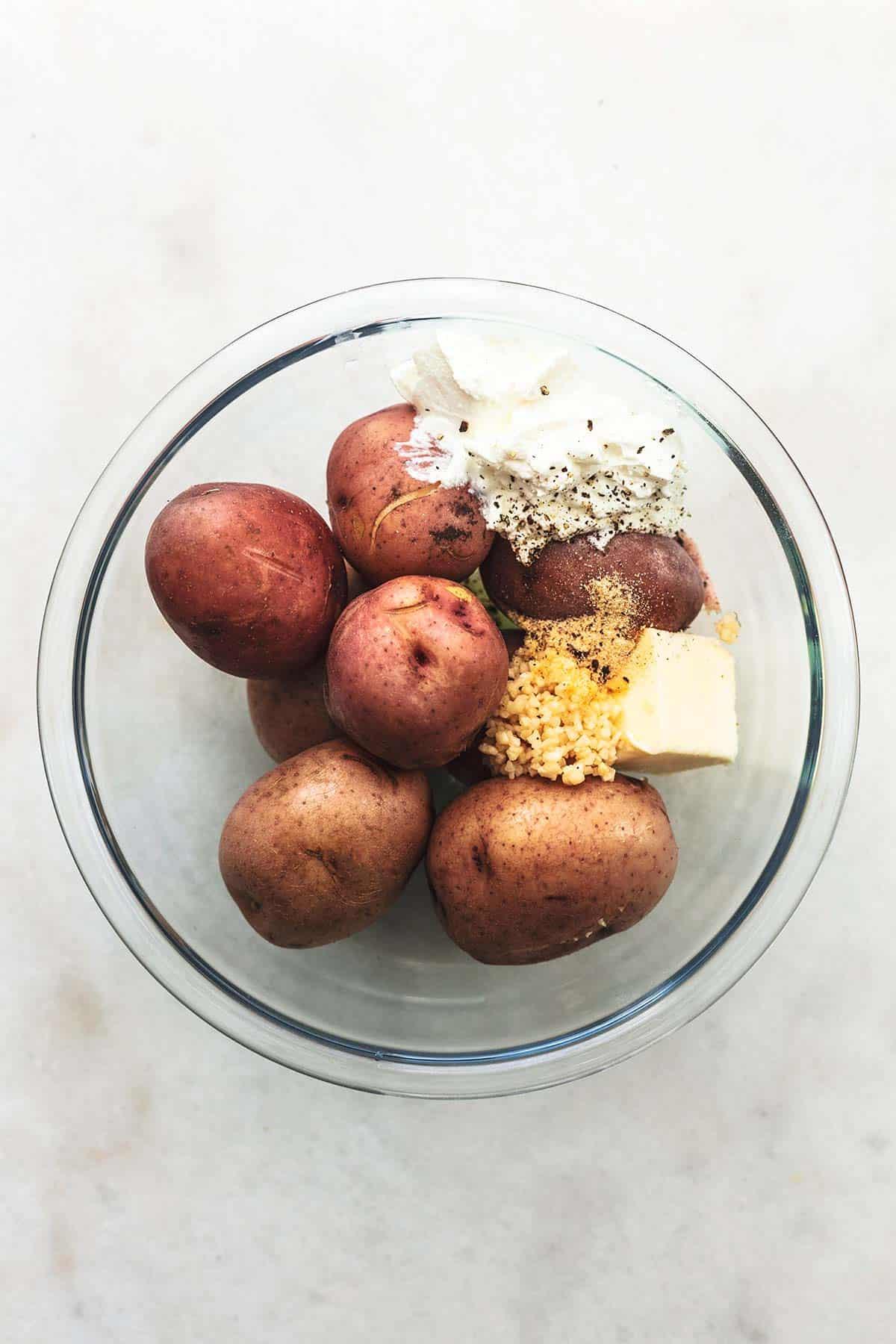 overhead view of potatoes, butter, sour cream, and garlic in a glass bowl
