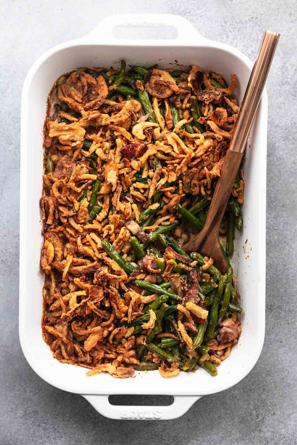 top view of green bean casserole with a serving spoon in a baking pan.