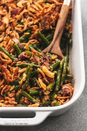 one corner of a white casserole dish filled with green bean casserole with wooden spoon
