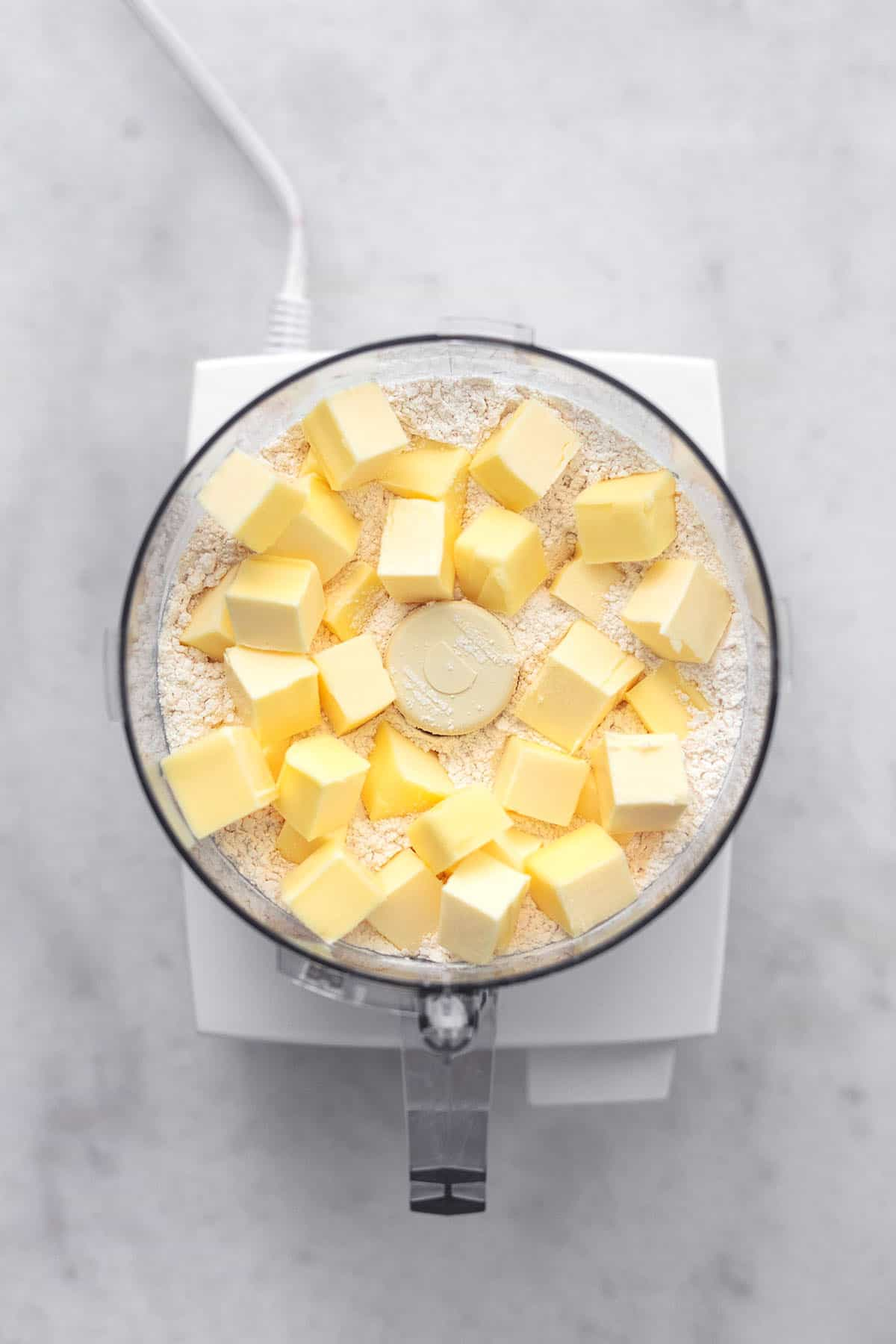top view of diced butter cubes and flour mixture in a food processor.