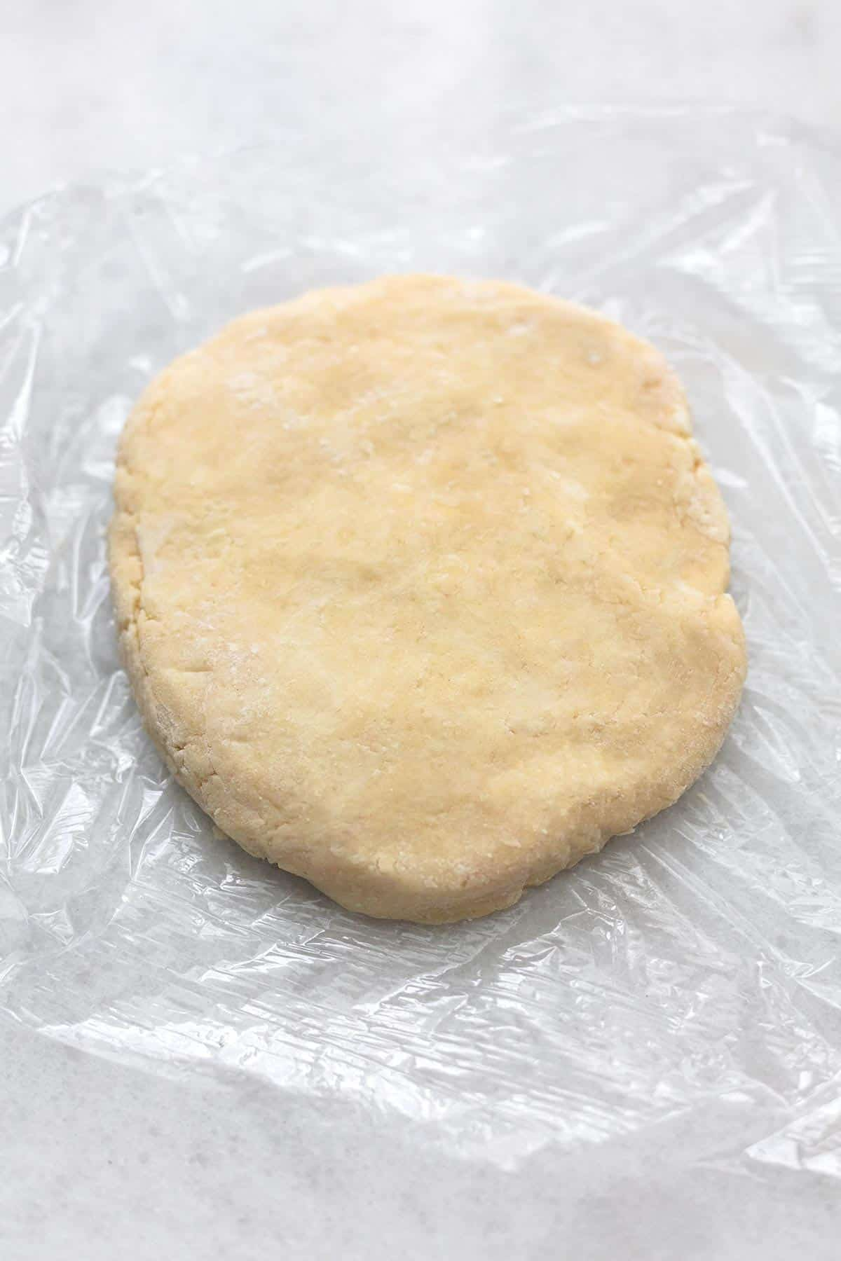 pie crust dough patted into a disc on plastic wrap.