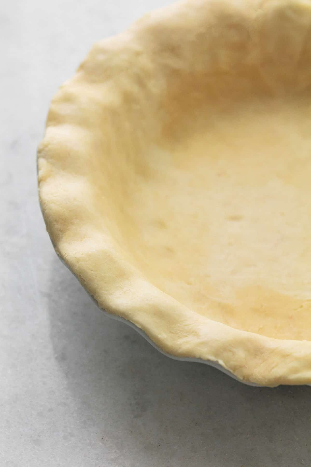 half of an unbaked pie crust with fluted edges