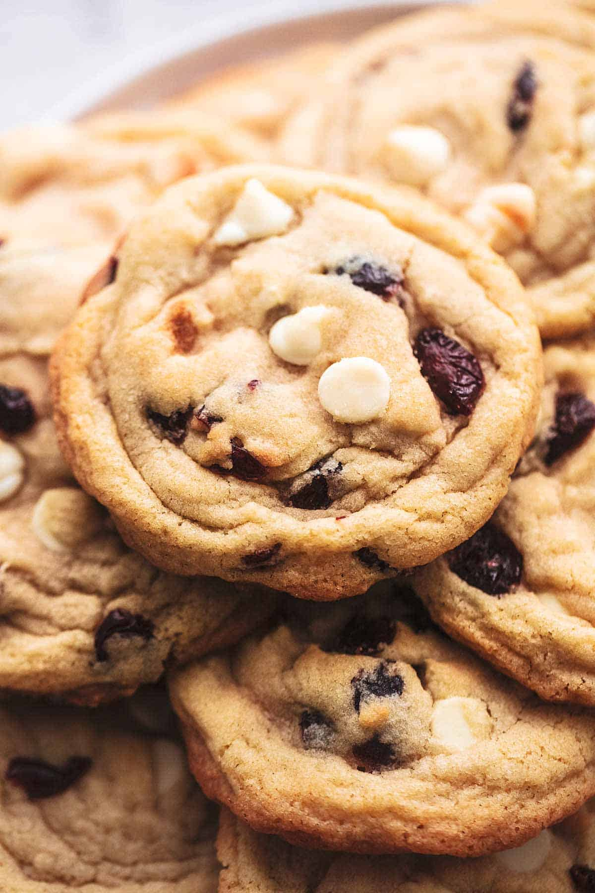 up close pile of cookies with white chocolate chips and cranberry pieces
