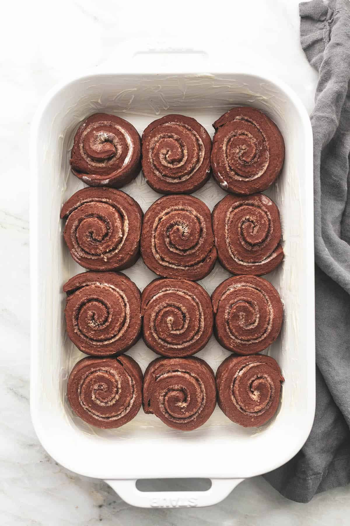 top view of unbaked chocolate cinnamon rolls in a baking pan.