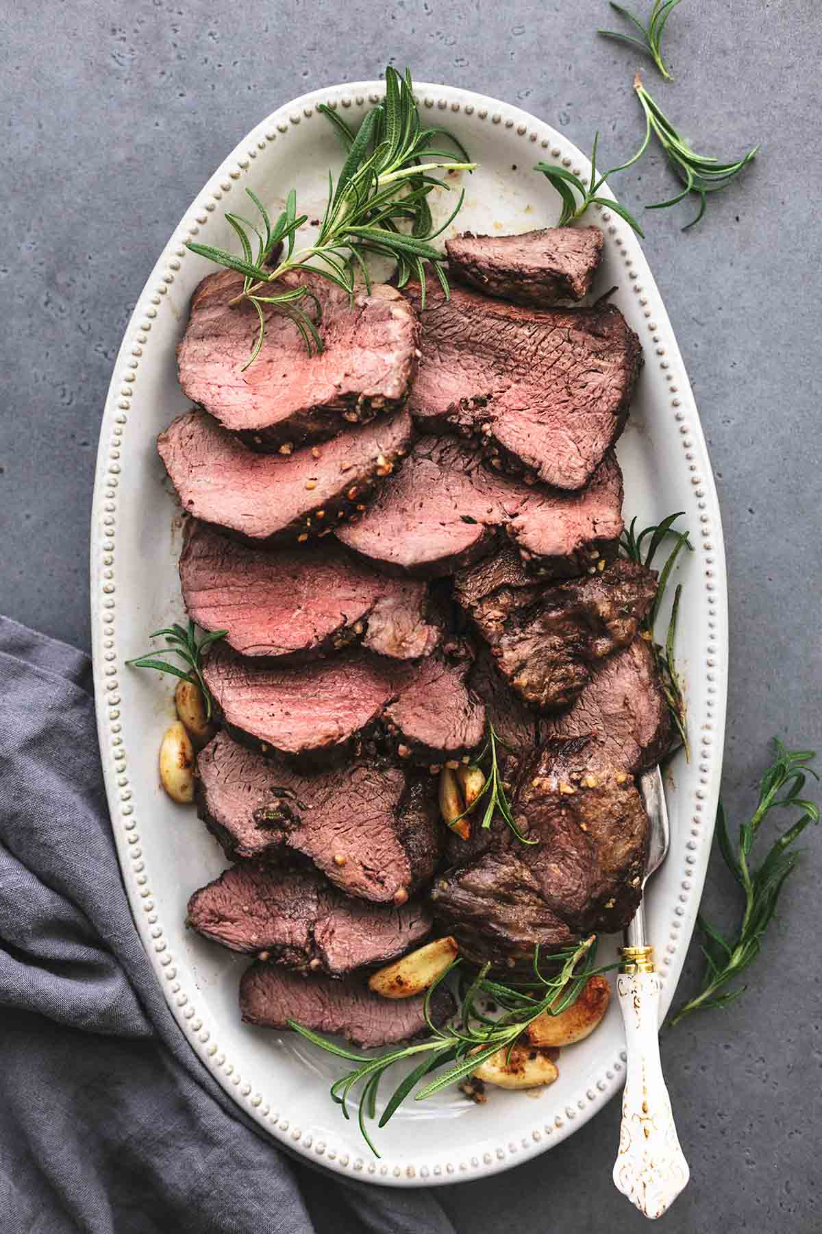 overhead view of sliced beef on beige serving platter with gray napkin on black table