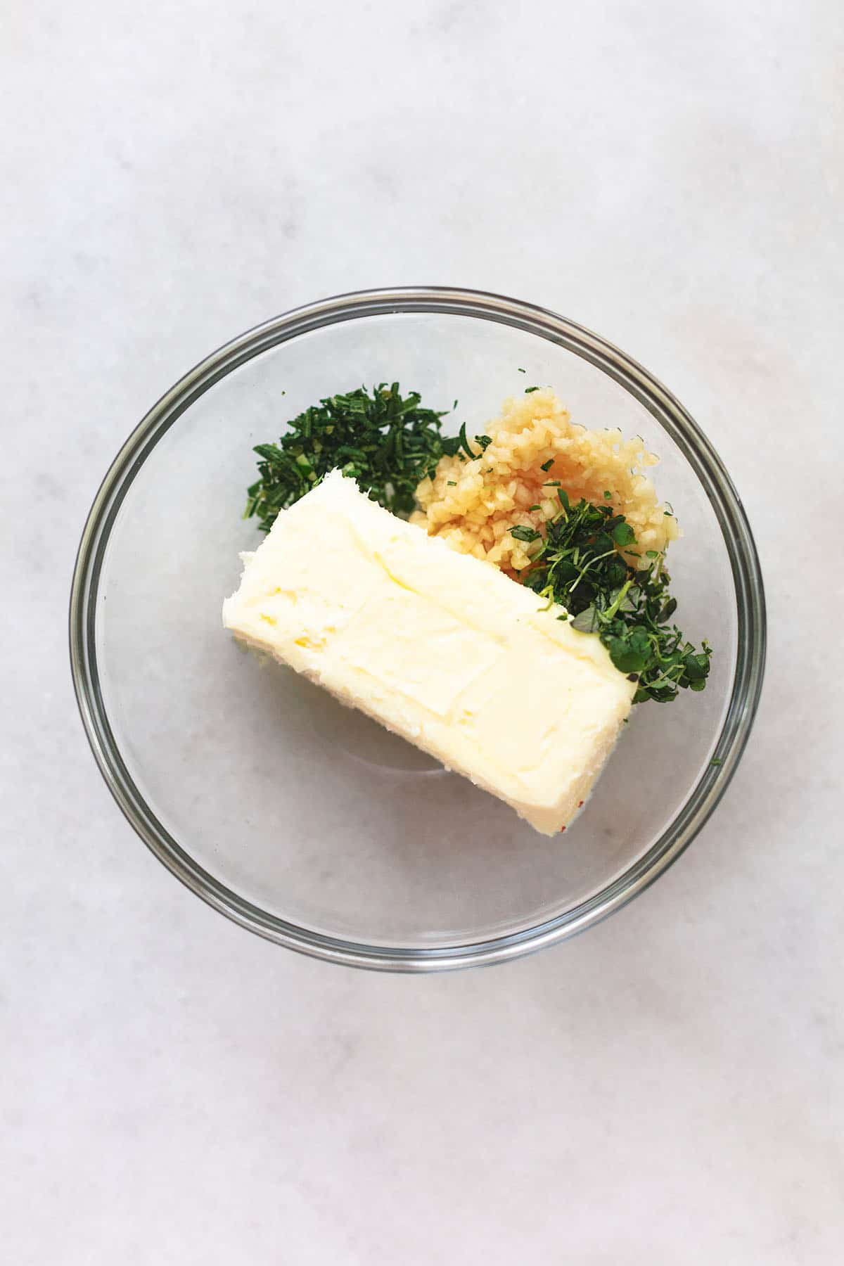 one stick of butter in glass bowl with fresh herbs and minced garlic