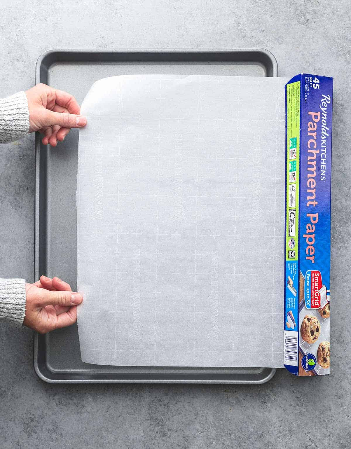 top view of hands pulling baking parchment from box above a baking sheet.