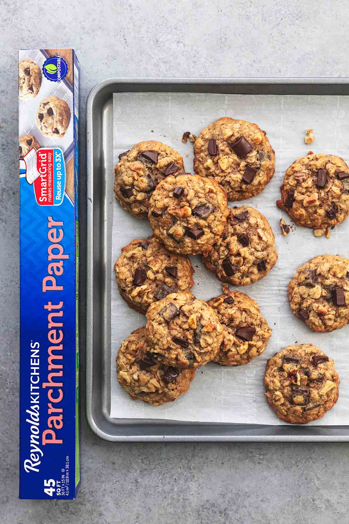 top view of chunky monkey banana cookies on a baking sheet beside a box of parchment paper.